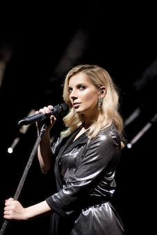 Mikrofon i wokalistka z bliska. kobieta śpiewa do mikrofonu.
