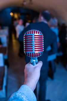 Mikrofon jest na scenie w klubie nocnym. piosenkarz trzyma i śpiewa do mikrofonu