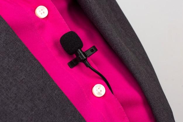 Mikrofon krawatowy jest zabezpieczony klipsem na zbliżeniu damskiej koszuli. nagranie dźwięku głosu na mikrofonie pojemnościowym