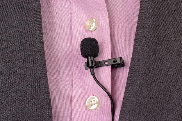 Mikrofon krawatowy jest zabezpieczony klipsem na zbliżeniu damskiej koszuli.