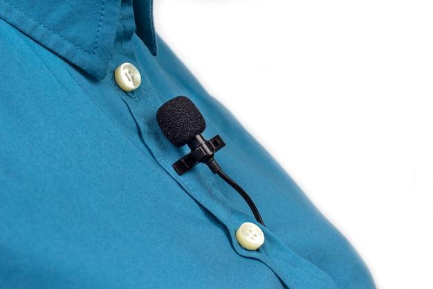 Mikrofon lavalier jest zabezpieczony klipsem na niebieskiej damskiej koszuli z bliska. nagranie dźwięku głosu na mikrofonie pojemnościowym.