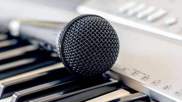 Mikrofon leży na klawiszach fortepianu, motyw muzyczny