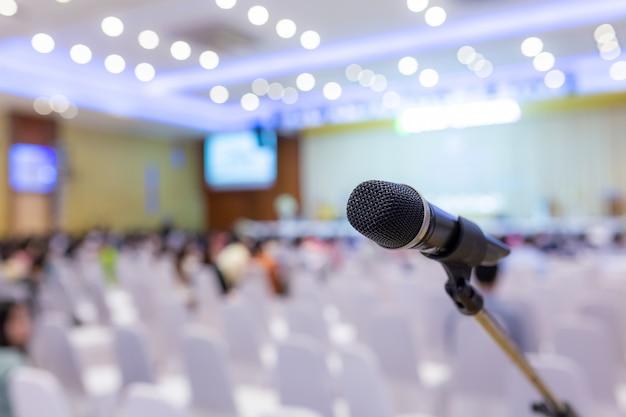 Mikrofon na abstrakcyjne niewyraźne zdjęcie sali konferencyjnej lub sali seminaryjnej