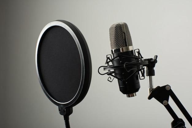 Mikrofon na stojaku z dyfuzorem na białym tle