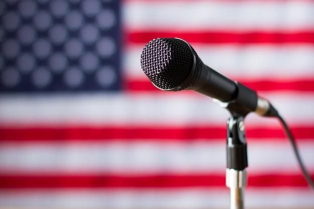 Mikrofon na tle flagi usa. baner i mikrofon z przewodem. prawda wkrótce zostanie ogłoszona. transmisja dla obywateli amerykańskich.