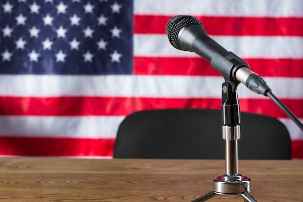 Mikrofon na tle flagi usa. flaga, mikrofon i krzesło. miejsce pracy gospodarza wiadomości. program telewizyjny zaraz się rozpocznie.