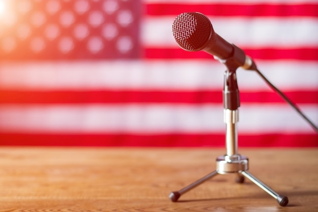 Mikrofon na tle flagi usa. stolik z mikrofonem i banerem. rozpoczyna się audycja radiowa. dzień dobry, współobywatele.
