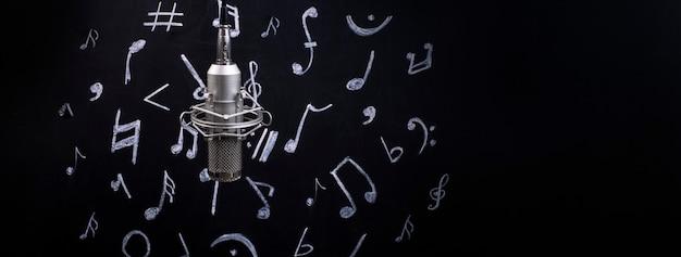 Mikrofon na tle tablicy do kredy z namalowanymi notatkami, obraz panoramiczny z miejscem na tekst, koncepcja czasu na muzykę