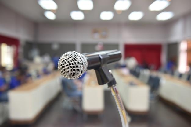 Mikrofon nad abstrakcyjnym niewyraźnym zdjęciem sali konferencyjnej lub sali seminaryjnej w exhibition center
