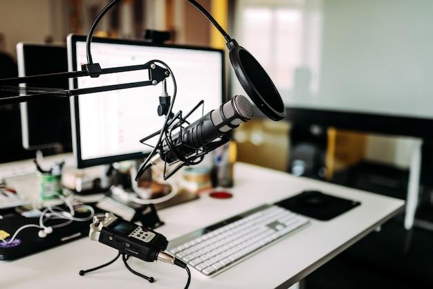 Mikrofon nad biurkiem w studiu radiowym.