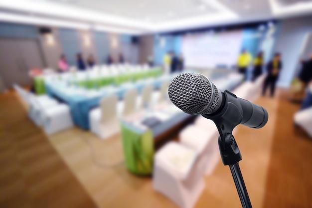 Mikrofon nad zamazanym biznesowym forum spotkaniem lub konferencyjnym stażowym uczenie trenowania pokoju pojęciem, zamazany tło.