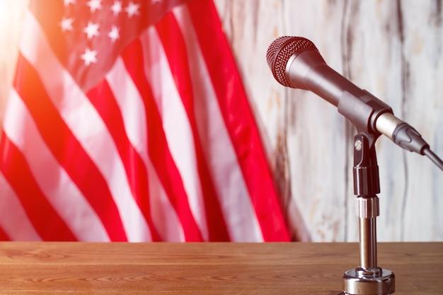 Mikrofon obok amerykańskiej flagi. banner behing stół z mikrofonem. czas rozpocząć prezentację. głos ludu.