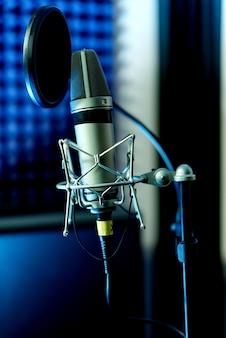 Mikrofon pojemnościowy studyjny z bliska z filtrem pop i antywibracyjnym nagrywaniem na żywo z kolorowymi światłami. widok z boku