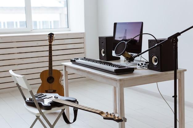 Mikrofon, sprzęt komputerowy i muzyczny, gitary i fortepian. koncepcja domowego studia nagrań.
