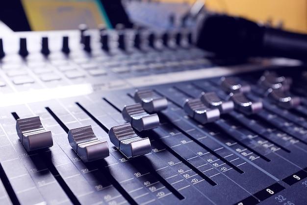 Mikrofon, sprzęt wzmacniający, pokrętła i suwaki miksera studio audio. sprzęt dla inżyniera dźwięku. akustyczne miksowanie muzyki, selektywne ustawianie ostrości. zdjęcie jest pokryte piaskiem i hałasem.