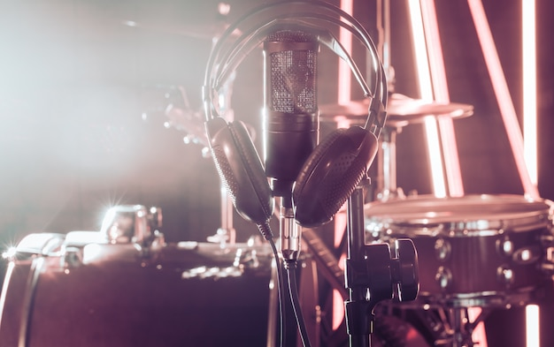 Mikrofon studyjny i słuchawki na stojaku z bliska, w studiu nagraniowym lub w sali koncertowej.