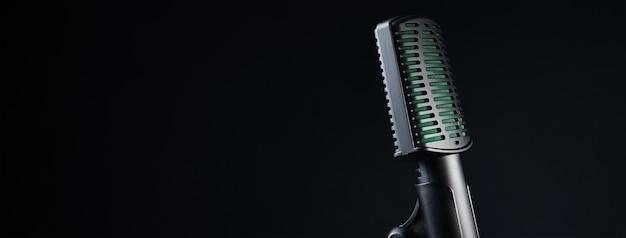 Mikrofon studyjny na czarnej ścianie, z bliska
