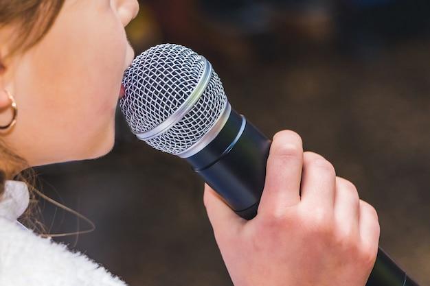 Mikrofon w dłoni na dziewczynę podczas piosenki