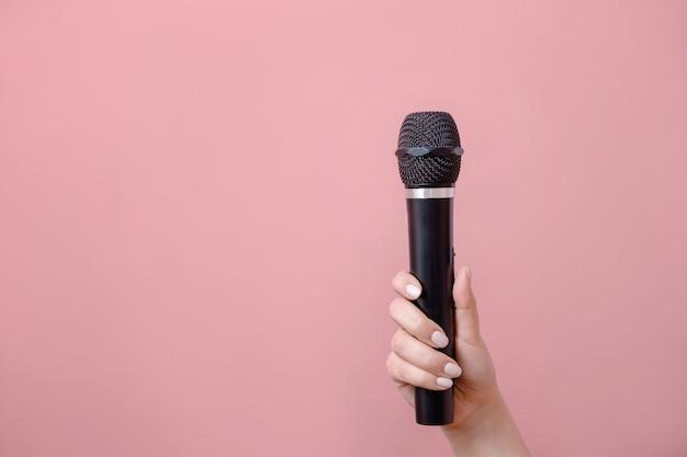 Mikrofon w kobiecej dłoni na różowym tle