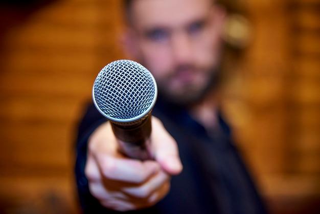 Mikrofon w ręce brodatego młodego człowieka.