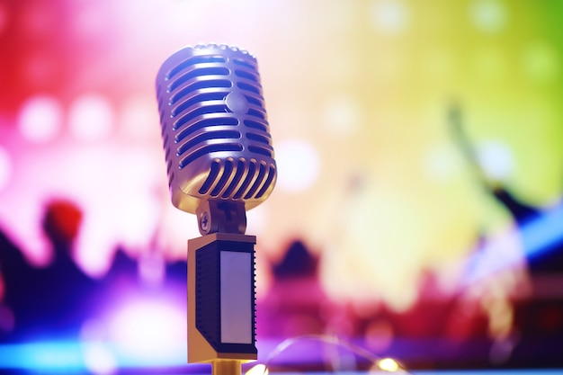 Mikrofon w stylu retro na tle z podświetleniem. vintage srebrny mikrofon do dźwięku, muzyki, karaoke. sprzęt do transmisji mowy. występ muzyczny pop, rock na żywo. selektywne skupienie
