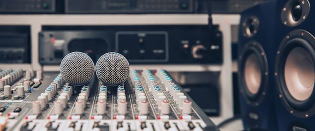 Mikrofon z bliska jest umieszczony na profesjonalnym mikserze audio w studio.