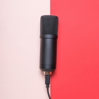 Mikrofon z podłączonym przewodem na czerwono-różowej powierzchni