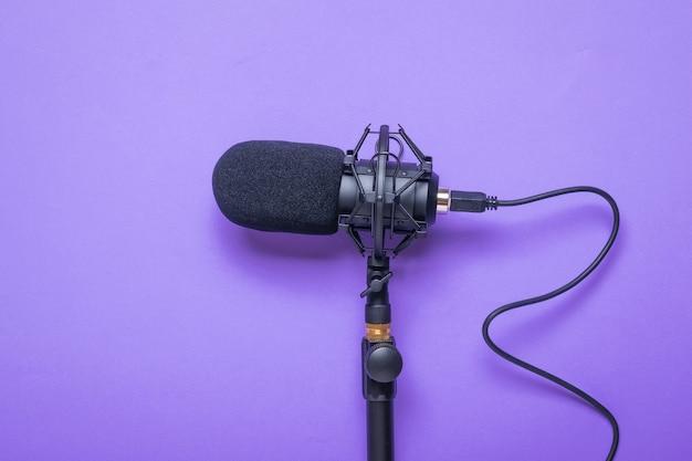 Mikrofon z przewodem przykręconym do statywu na fioletowej powierzchni
