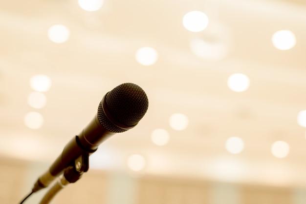 Mikrofon znajduje się na podium w sali konferencyjnej lub seminaryjnej ze światłem bokeh
