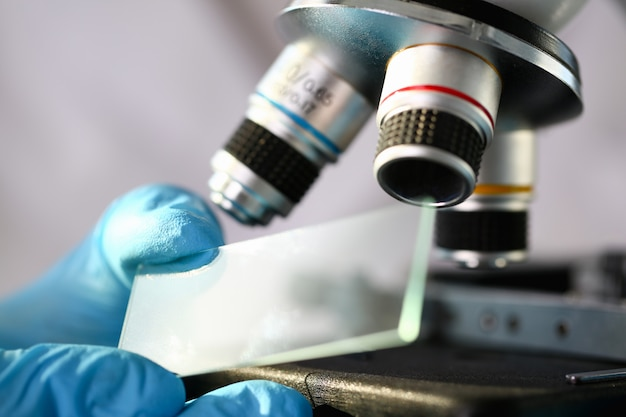 Mikroskop głowy w tle laboratorium to badanie analiz biologii człowieka pod kątem niezgodności z wymogami organizacji zdrowia publicznego na poziomie międzynarodowym