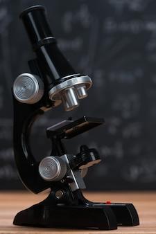 Mikroskop szkolny na tle drewna i tablicy napisany wzorami matematycznymi i równaniami