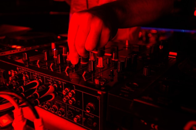 Mikser dj w jasnym czerwonym świetle. wytnij bliska strzał męskiej ręki obracając bębny na konsoli dysku dżokeja. koncepcja życia nocnego. rave na imprezie przy dobrej muzyce.