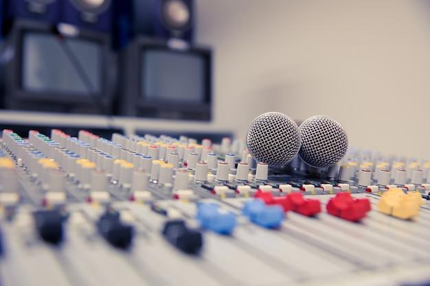 Mikser dźwięku i mikrofony powiązane w sali konferencyjnej.