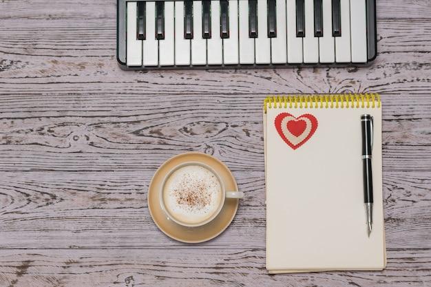 Mikser muzyczny, filiżanka kawy i notatnik na drewnianym stole. przerwa w pracy nad przetwarzaniem muzyki. leżał na płasko.
