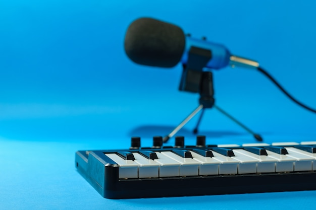 Mikser muzyczny i niebieski mikrofon z przewodami na niebieskiej powierzchni. sprzęt do nagrywania utworów muzycznych.