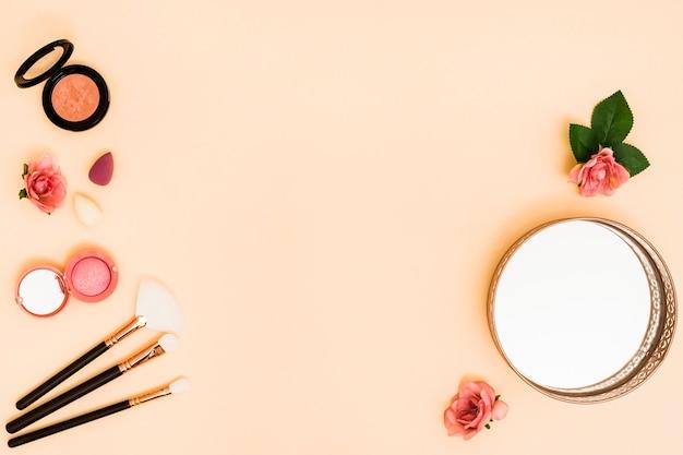 Mikser; pędzle do makijażu; róża; lustro i kompaktowy proszek na beżowym tle