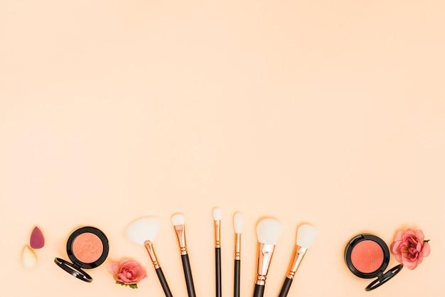 Mikser; pędzle do makijażu; róże; kompaktowy proszek na beżowym tle