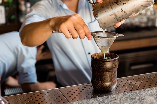 Miksolog robi koktajl z shakerem, wlewając przez filtr do drewnianej szklanki z kostkami lodu na barze koktajlowym.