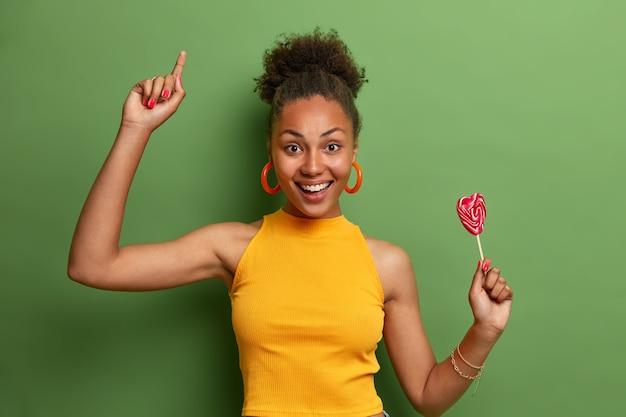Miła atrakcyjna, beztroska dziewczyna tańczy radośnie z lizakiem w kształcie serca, bawi się w domu, ma słodycze i dobry nastrój po zjedzeniu pysznych cukierków, porusza się z radością po żywej zielonej ścianie
