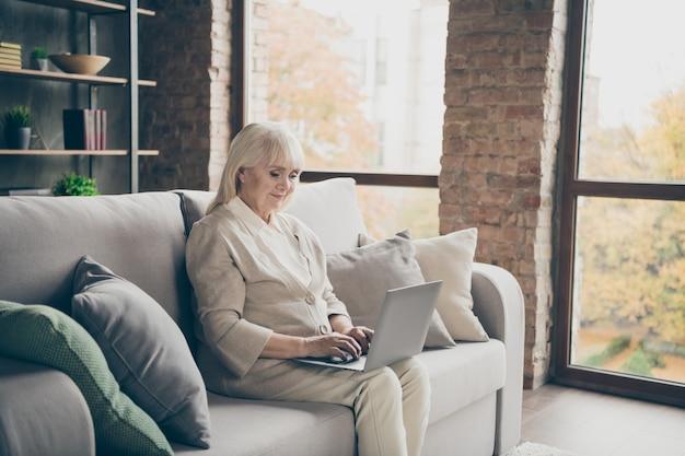 Miła atrakcyjna spokojna, skupiona na sobie, siwowłosa pani siedząca na sofie, pisząca na klawiaturze, tworząca nowatorskie projekty internetowe w industrialnym ceglanym lofcie nowoczesny styl wnętrza salonu