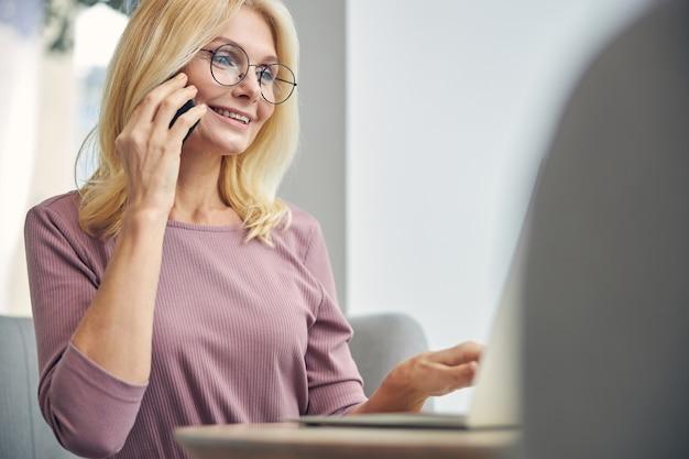 Miła blondynka z uśmiechem na twarzy, patrząc na ekran swojego laptopa
