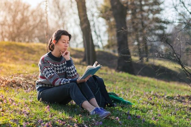 Miła brunetka dziewczyna siedzi na trawie w parku i czyta książkę.