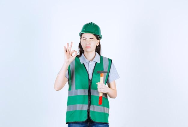 Miła brygadzistka trzymająca i mrugająca, robiąc znak ręką