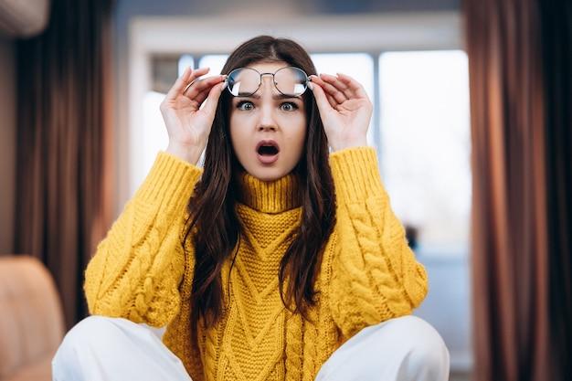 Miła dziewczyna w okularach i uroczym swetrze jest zaskoczona czymś, czego nie oczekuje pracujący jako freelancer w domu zdjęcie o młodej freelancerce pracującej w domu student uczy się online w domu