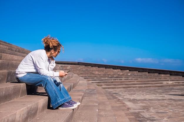 Miła dziewczyna wirująca brązowymi włosami siada w pięknym miejskim miejscu z panoramą nieba, korzystając z technologii telefonu komórkowego, aby pozostać w kontakcie z przyjaciółmi i ludźmi na całym świecie. nowoczesna nie tylko koncepcja