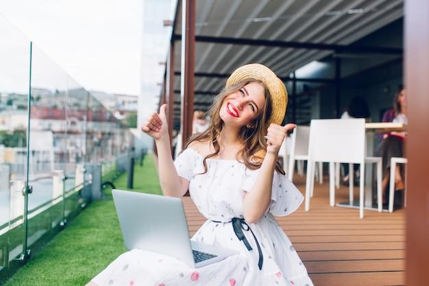 Miła dziewczyna z długimi włosami w kapeluszu siedzi na podłodze na tarasie. nosi białą sukienkę z odkrytymi ramionami i czerwoną szminką. ma laptopa na kolanach i wygląda na szczęśliwą.