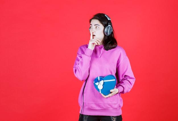 Miła dziewczyna ze słuchawką trzyma prezent, przykładając dłoń do ust i rozglądając się dookoła