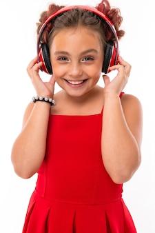Miła dziewczynka kaukaski w czerwonej sukience z dużymi słuchawkami słuchać muzyki na białym tle.