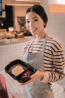 Miła kelnerka. promieniejąca miła kelnerka w pasiastym fartuchu trzymająca ładne pudełko na lunch dla klientów