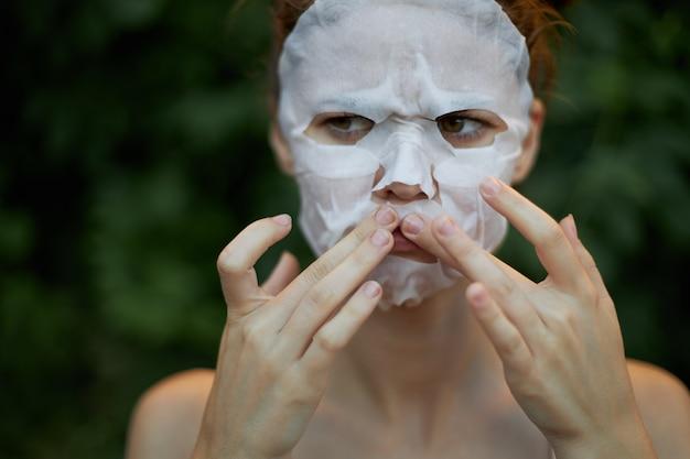 Miła kobieta maseczka przeciwzmarszczkowa dociśnij palcami w pobliżu ust dermatologia zielone krzaki